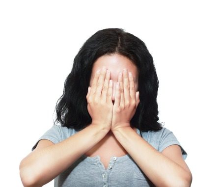 hands covering face: Pretty brunette woman covering her face with both hands
