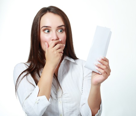 overspending: shocked young woman checking over the receipt and spending too much Stock Photo