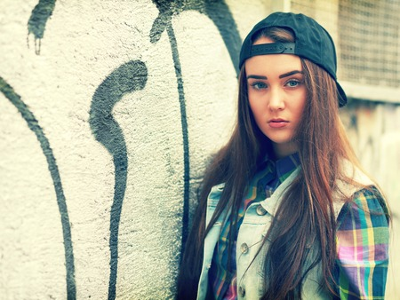 misfit: portrait of a skater style teenager girl with graffiti wall in the background toned image