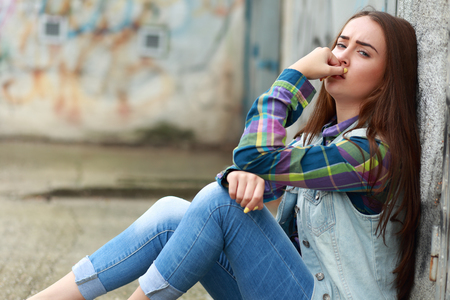 Beautiful young sad girl sitting on asphalt
