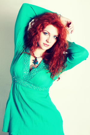 plus size woman: portrait of a beautiful woman with red curly hair. wearing a romantic green or turquoise dress Fashion retro toning.