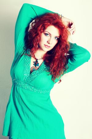 donne obese: ritratto di una bella donna con i capelli rossi ricci. indossa un abito romantico moda retrò tonificazione verde o turchese.