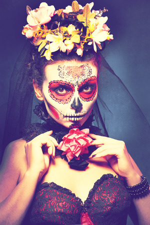 gothic girl: halloween make up sugar skull beautiful model with perfect hairstyle. Santa Muerte concept. Fashion retro toning. Stock Photo