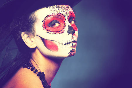 Sugar skull girl in hat halloween concept Fashion retro toning. Stock Photo