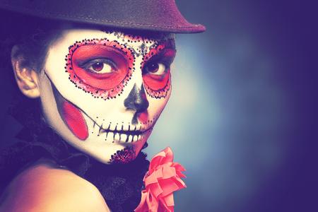 Muchacha del cráneo del azúcar en el sombrero, estudio tiro Moda tonificación retro.