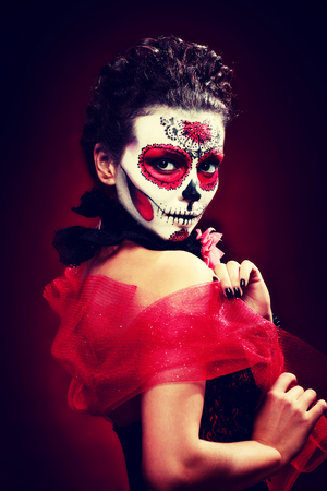 halloween make up sugar skull beautiful model with perfect hairstyle. Santa Muerte concept. Fashion retro toning. Stock Photo