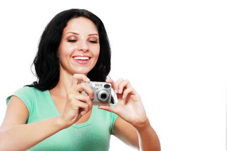compact camera: young and beautiful woman with compact camera looking to its screen