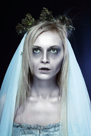 portrait of beautiful zombie corpse bride looked scary and standing at dark background halloween concept