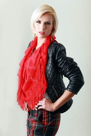 high fashion model: high fashion model wearing leather jacket and red scarf posing over white background