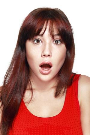 extrañar: Close-up retrato de la muchacha hermosa sorprendida sosteniendo su cabeza con asombro y con la boca abierta. Sobre fondo blanco.