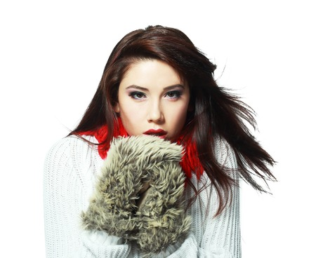 sexy young girl: beautiful young woman feeling cold wind in winter hearing warm closthes and fur gloves isolated over white Фото со стока
