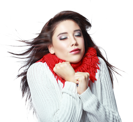 cold weather: beautiful young woman feeling cold wind in winter hearing warm closthes isolated over white Stock Photo