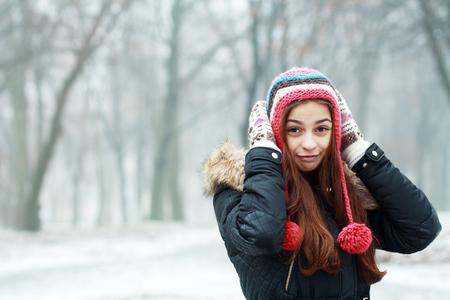 frio: Retrato de la muchacha sonriente joven bastante divertido en tiempo frío vestida con ropa de color y sombrero caliente. Mujer feliz joven que se divierte al aire libre. Copyspace