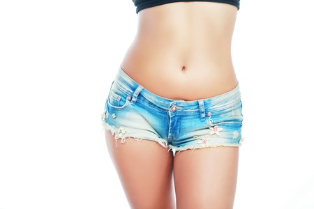 loose skin: female body on ripped shorts belly detail isolated white background