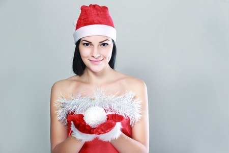 snow ball: Beautiful happy woman in Santa Claus clothes holding snow ball