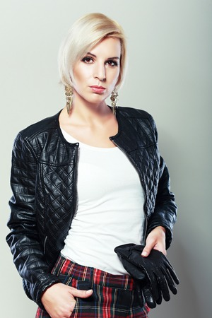 female hand: female model wearing leather jacket and red scarf posing fashion in the studio