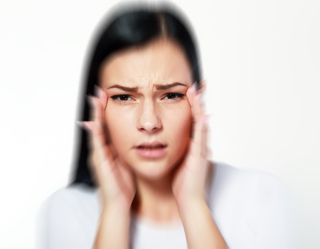 beautiful young woman over white with blurred vision and trouble focusing, trying to get focus on eyes with hands Stockfoto