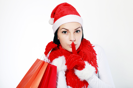 noiseless: pretty girl holding shopping bags and asking silence with her finger keeping a secret about something Stock Photo