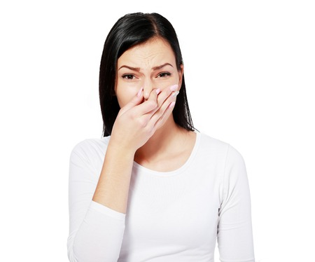pinches: Closeup portrait young woman, disgust on face, pinches nose looks funny, something stinks, very bad smell, situation, isolated white background Stock Photo