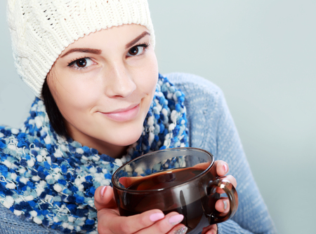tied woman: Young woman in warm sweater, colorful scarf, white cap with big hot cup of tea.