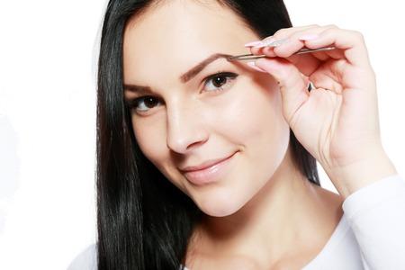 brow: young beautiful woman eyebrow plucking tweezers brow hair closeup portrait