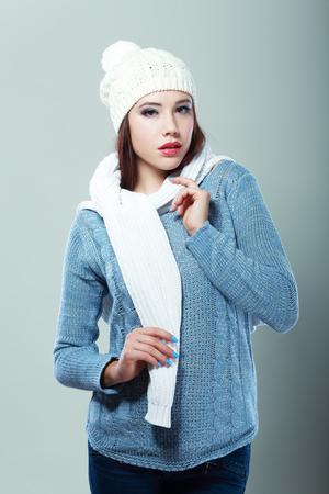 beautiful smiling mixed race caucasianasian female model wearing a blue woolen sweater