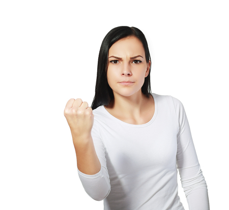 threatens: The portrait the young beautiful woman threatens with a fist is isolated on white