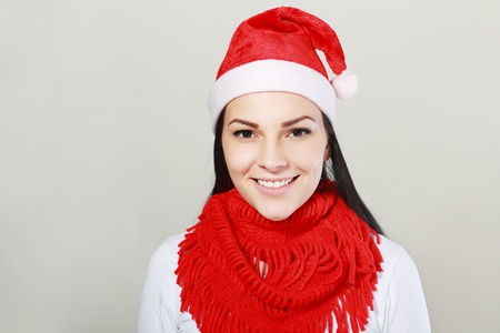 girl in red dress: close up portrait of a smiling beautiful happy girl in christmas santa hat. beauty woman. isolated on white background. happy new year 2016. Stock Photo