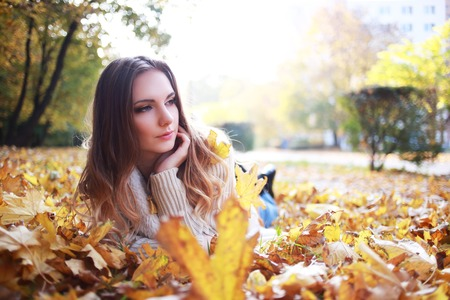 woman laying down: Image of cheerful young woman laying down on the ground covered dry autumnal foliage in beautiful park