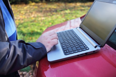 men at work: Male outsourse worker,  hand on notebook laptop outdoor close up. Freelance outsourse job. Work from home Stock Photo