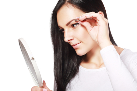 tweezing eyebrow: young beautiful woman eyebrow plucking tweezers brow hair closeup portrait