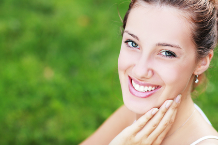 dentistry: Candid woman with perfect teeth and smile looking you with the wind moving her hair