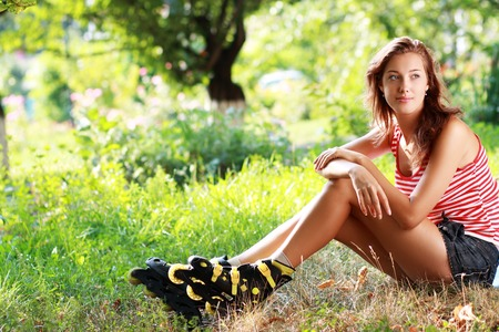 roller: girl wearing roller skates sitting on grass in the park Stock Photo