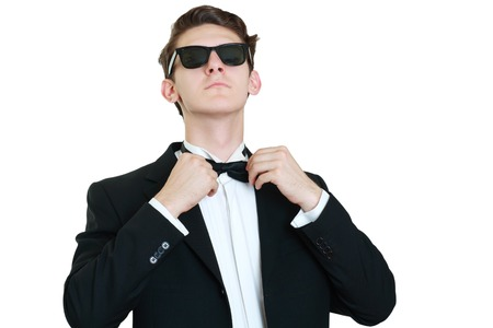sex symbol: Used to perfection. Handsome young man in formalwear adjusting his bow tie while standing against grey background