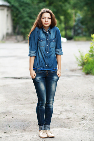 beautiful teen girl standing outdoor in jeans and checked shirt