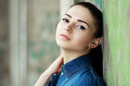 lonely woman: Lonely teenage girl leaning against concrete wall in urban environment.