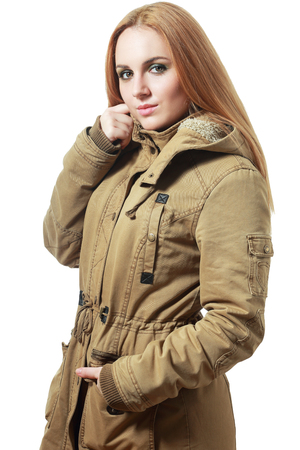 beautiful girl with long hair in a khaki coat on an isolated background