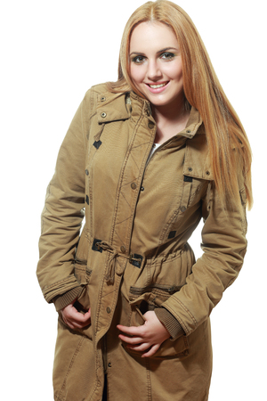 mackintosh: beautiful girl with long hair in a khaki coat on an isolated background