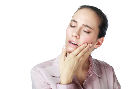 amalgam: Closeup portrait young woman with sensitive tooth ache, crown problem about to cry from pain, touching outside mouth with hand, isolated white background. Negative emotions, facial expression, feeling