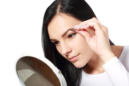tweezing eyebrow: Beautiful girl tweezing eyebrow isolated over white
