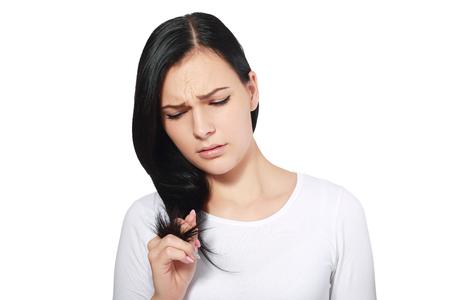 brunette vrouw is niet gelukkig met haar breekbaar haar, witte achtergrond, copyspace Stockfoto