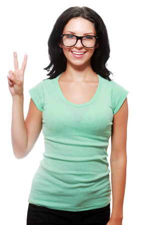 one people: Happy smiling beautiful young student woman in glasses showing two fingers or victory gesture, isolated against white background