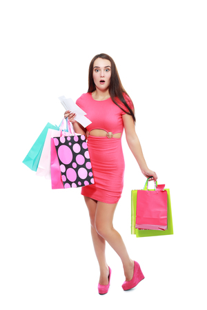 too: young woman shocking after checking over the receipt in her hands and spending too much Stock Photo