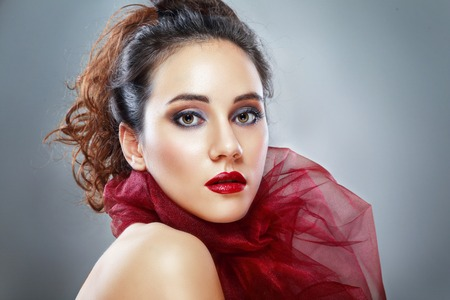 red scarf: beauty portrait of the young beautiful woman in red scarf Stock Photo