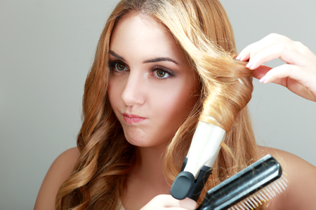 curling irons: Portrait of young beautiful girl doing hairstyle and purse her lips Stock Photo