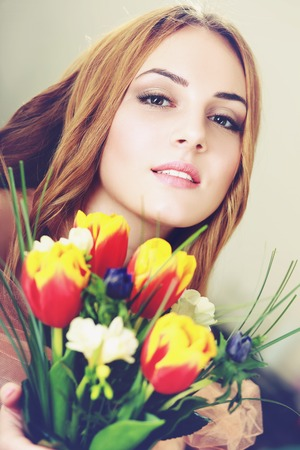 flower head: smiling woman got flowers for womans day Stock Photo