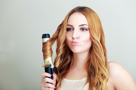 styler: Portrait of young beautiful girl doing hairstyle and purse her lips Stock Photo