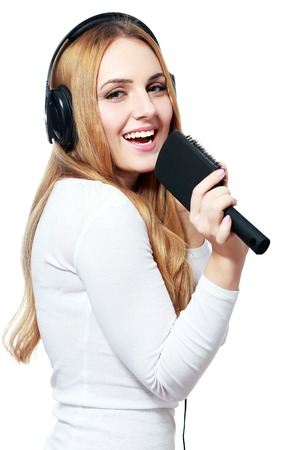 earbud: playful woman listening to music playing through her stereo earbud headphones and pretending to sing on a microphone that is actually a hair brush.