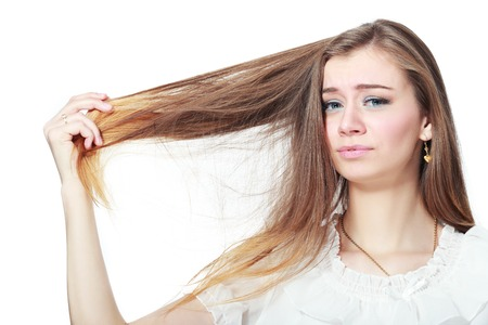dry hair: Portrait of woman holding damaged dry hair and sad looking isolated on grey background