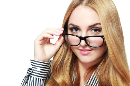 peering: Model Released. Young Business Woman Peering Over Glasses